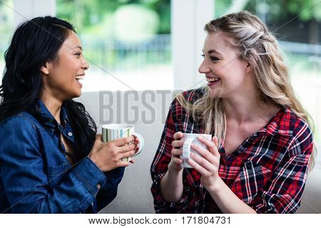 Cheerful young female friends drinking coffee while sitting on sofa at home
