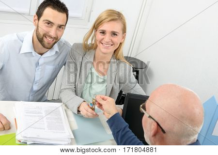 a young smiling couple buys an apartment
