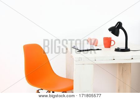 White vintage wooden table with black lamp open notepad orange mug and pink pig moneybox on it orange chair nearby isolated on white background. Workplace conception