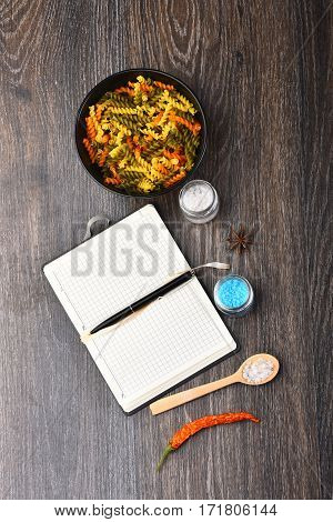 Open Notebook With Pen And Colorful Fusilli