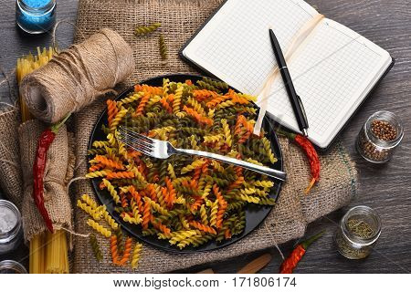 Fusilli Pasta And Open Notebook With Pen