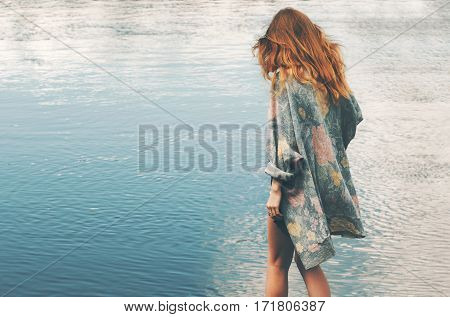 Young red hair woman walking at river alone wearing long cardigan Fashion Lifestyle concept and melancholy depression emotions