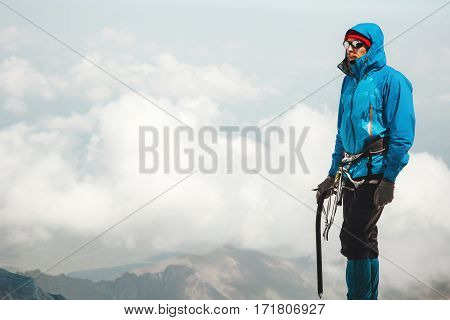 Man climber with ice axe standing on mountain summit Travel Lifestyle concept adventure active vacations outdoor mountaineering sport alpinism equipment