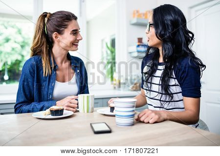 Happy young female friends talking while having breakfast at table in house