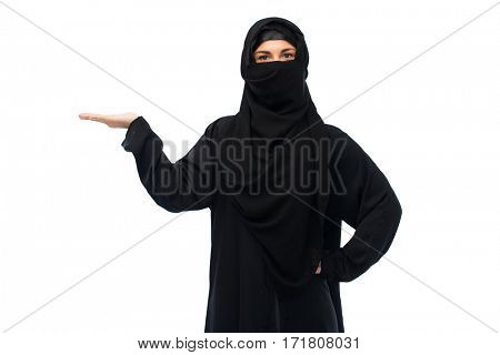 religious and people concept - muslim woman in hijab holding empty hand over white background