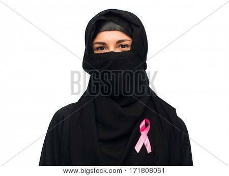 medicine, healthcare and people concept - smiling muslim female doctor wearing hijab and white coat with pink breast cancer awareness ribbon
