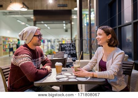 people, lifestyle and dating concept - happy couple drinking coffee and smoothie at cafe