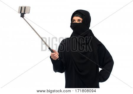 technology and people concept - muslim woman in hijab taking picture with smartphone selfie stick over white background