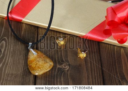 Closeup big pendant and stud earrings in forms of butterflies from authentic baltic amber and silver on wooden table amid gift box with red ribbon