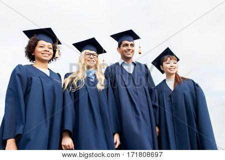 education, graduation and people concept - group of happy international students in mortarboards and bachelor gowns outdoors