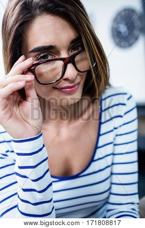 Close-up portrait of confident young woman wearing eyeglasses at home