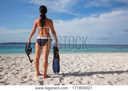 Girl in bikini with snorkeling gear on the beach Maldives.