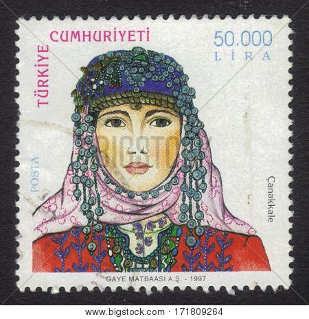 Turkey - CIRCA 1997: A stamp printed in Turkey shows portrait of girl from the Canakkale Province in a traditional turkish headdress, circa 1997