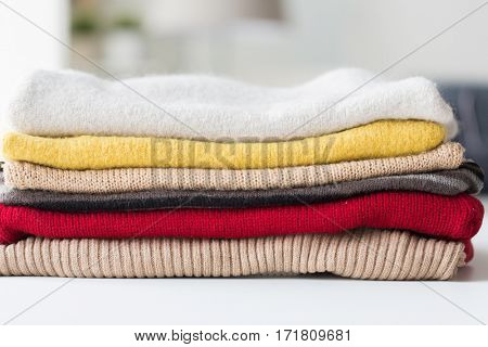 laundry, clothing, household and objects concept - close up of stacked knitted clothes