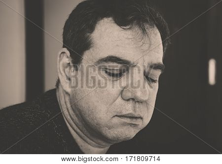 Vintage style black and white monochrome portrait. Mature sad man.