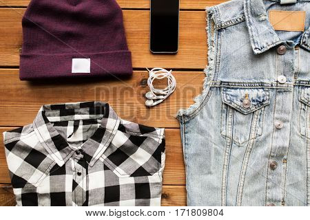 clothing, personal staff and objects concept - clothes and smartphone with earphones on wooden background