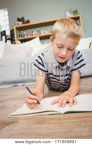 Close-up of boy writing in book while lying on hardwood floor at home