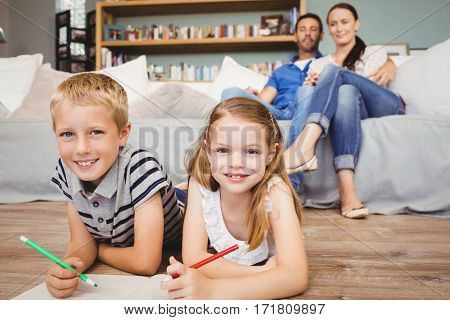 Portrait of happy children coloring on book while parents sitting at sofa in living room
