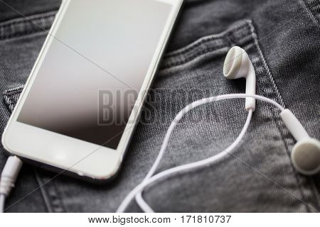 technology and music concept - smartphone and earphones on pocket of denim pants or jeans