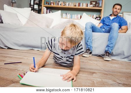 Close-up of boy drawing in book while father sitting on sofa at home