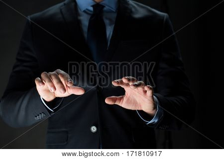 business, people, technology, cyberspace and office concept - close up of businessman in suit working with invisible virtual reality screen