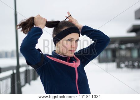 Sporty girl have work out fitness at snow winter promenade - straightens hair, telephoto