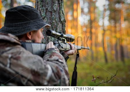 Hunter looking into rifle scope and getting ready to shoot poster