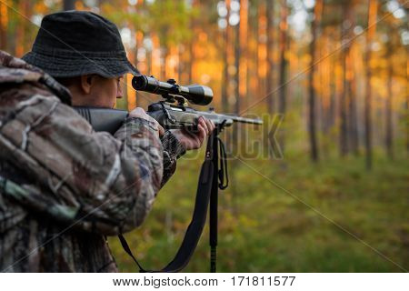 Hunter aiming with rifle in the far