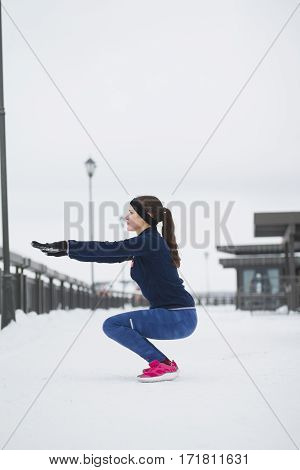 Fitness girl have work out fitness at snow winter promenade, vertical