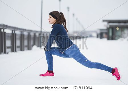 Young woman runner doing flexibility exercise for legs before run at snow winter promenade, telephoto