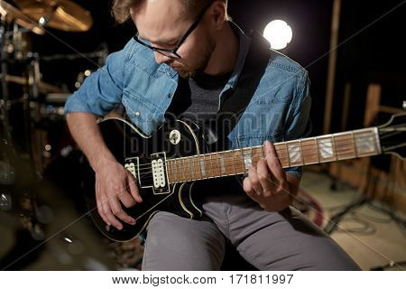 music, people, musical instruments and entertainment concept - male guitarist playing electric guitar at studio rehearsal