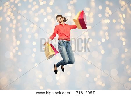 sale, motion and people concept - smiling young woman with shopping bags jumping in air over holidays lights background