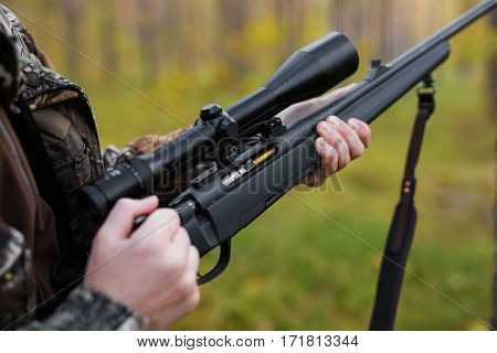 Hunter loading his gun with bullets for hunting session