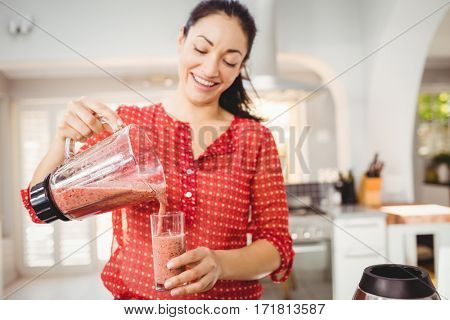 Smiling woman pouring fruit juice in glass while standing at home