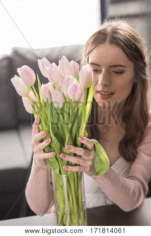Young woman putting bouquet of fresh tulip flowers in vase and smiling