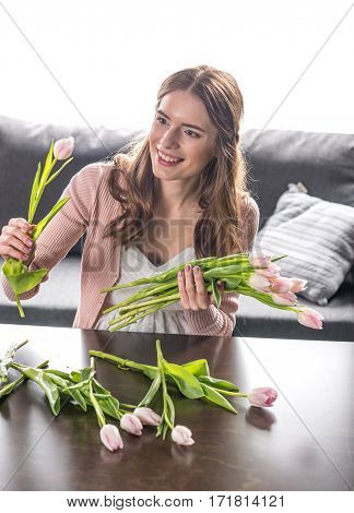 Young smiling woman sitting at table and collecting bouquet of fresh tulip flowers