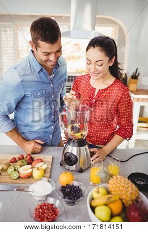 Smiling couple preparing fruit juice while standing at table in home
