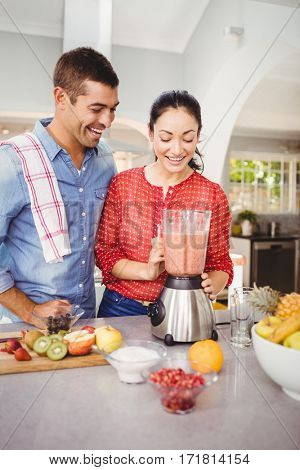 Laughing couple with fruit juice while standing at home