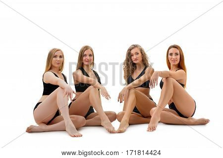 Pretty girls in black tops and shorts posing together sitting gracefully on the floor studio shot