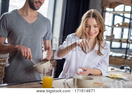 Young couple cooking together with eggs and flour in kitchen