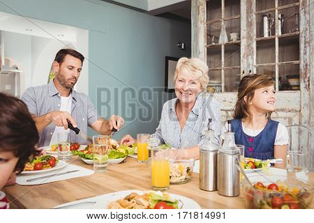 Smiling granny while sitting at dining table with family