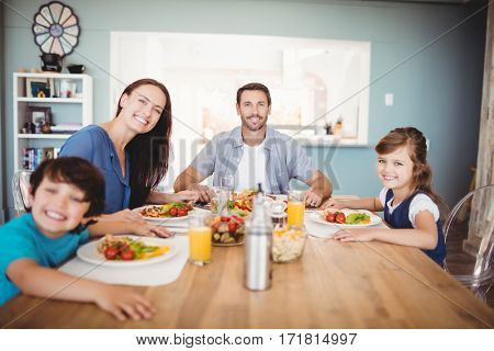 Portrait of smiling family with food on dining table at home