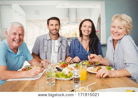 Portrait of family sitting at dining table with food in home