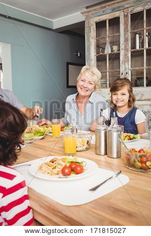 Portrait of smiling granny and granddaughter sitting at dining table with family