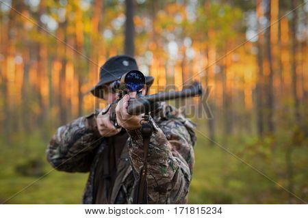 Hunter shooting a shotgun in the woods