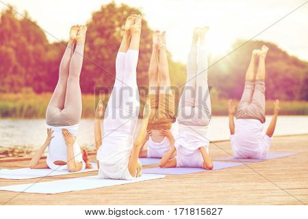 fitness, sport, yoga and healthy lifestyle concept - group of people making shoulderstand pose on river or lake berth