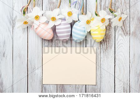 Easter eggs and fresh spring daffodils on white wooden background. Easter card.