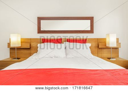A Bright and Fresh Bedroom Suite With Red Blanket and Pillows