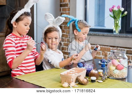 Three adorable little kids in bunny ears painting easter eggs