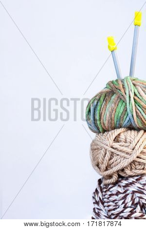 Close Up Of Three Threads For Knitting White And Brown Colors And Spokes On White Background Copyspace.